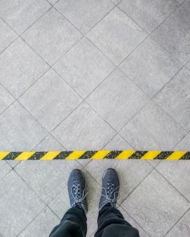 Черные туфли, стоящие на асфальтобетонном полу с оранжевой линией. ноги обуви прогулки на открытом воздухе. молодежный селфи современный хипстер