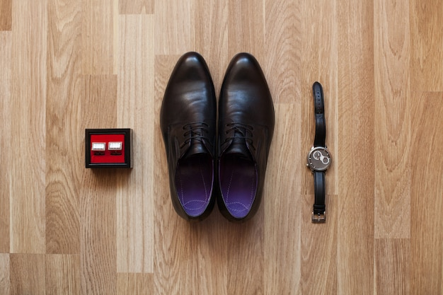 床に黒い靴、時計、カフリンクス。結婚式の日に新郎のためのアクセサリー。