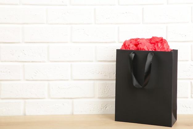 Black shopping bag on a light wall.