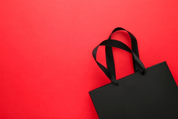 Black shopping bag on a red .