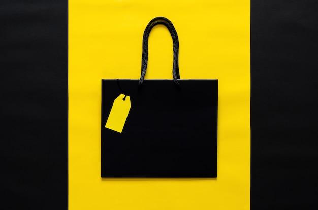 ブラックフライデーのショッピングセールのコンセプトのための黄色と黒の背景に空白の黄色の値札が付いた黒いショッピングバッグ。