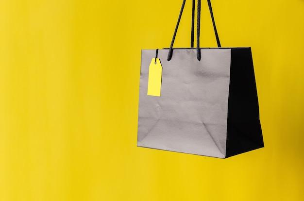 ブラックフライデーのショッピングセールのコンセプトのための黄色の背景を持つ空白の黄色の値札が付いた黒いショッピングバッグ。