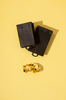 검은 금요일 판매에 있는 검은색 쇼핑백은 축제 화환이 있는 노란색 배경에 평평하게 놓여 있습니다.