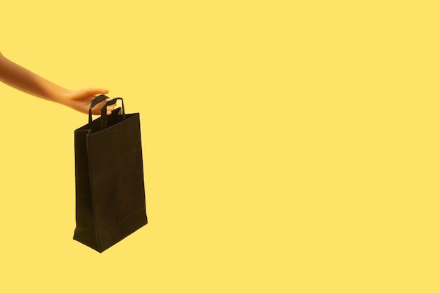 노란색 배경에 복사 공간이 있는 인형 손에 검은 금요일 판매에 검은색 쇼핑백