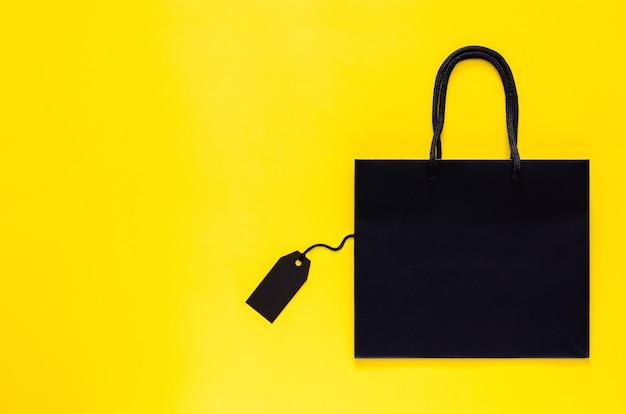 ブラックフライデーのショッピングセールのコンセプトの黄色の背景に空白の黒の値札が付いた黒のショッピング紙袋。