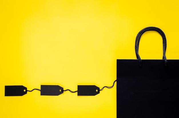 ブラックフライデーのショッピングセールのコンセプトのための黄色の背景に空白の黒い値札が付いた黒いショッピング紙袋。