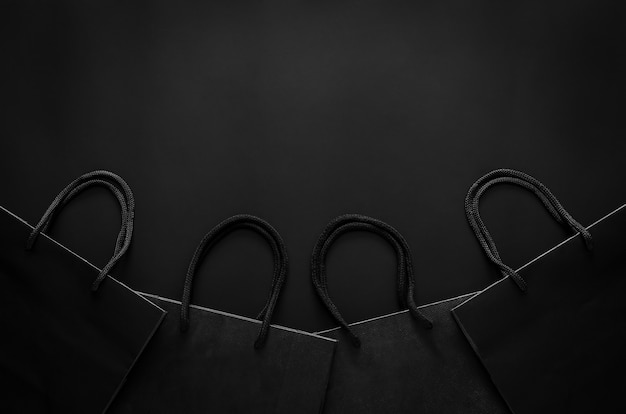 ブラックフライデーのショッピングセールのコンセプトの黒の背景に黒のショッピング紙袋。
