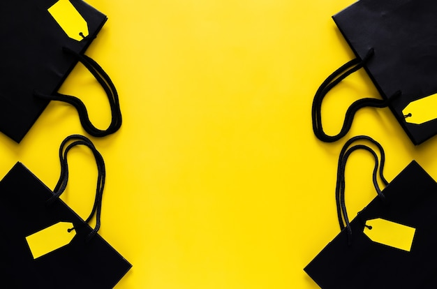 ブラックフライデーのショッピングセールのコンセプトのための黄色の背景に空白の黄色の値札が付いた黒いショッピング紙袋。