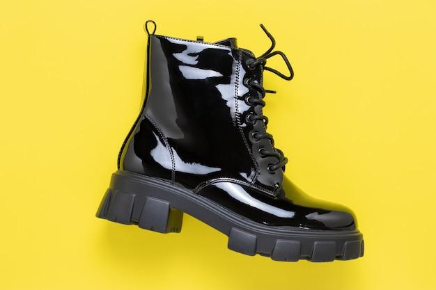 黄色い表面に黒いショートブーツ。パテントレザーの靴。秋の女性のレースアップシューズ。トラクターソールのモダンなアウトドアブーツ。カジュアルなファッションコンセプト。