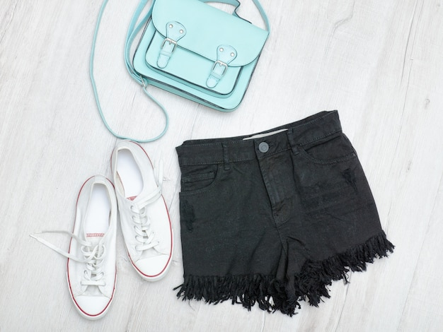 Black shorts and sneakers, mint bag. fashionable concept. wooden table.