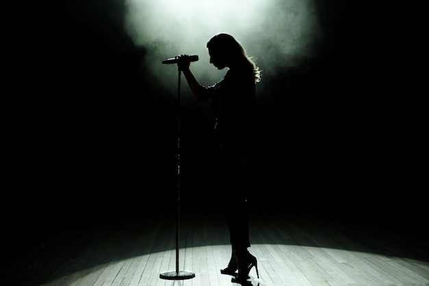 Black silhouette of female singer with white spotlights in the background