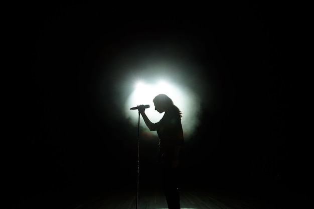 Black silhouette of female singer with white spotlights in the background.