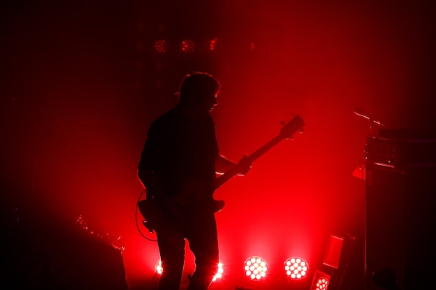 Black silhouette of guitarist at rock concert