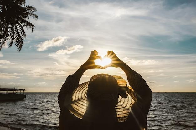 スーとまっすぐに彼女の指で愛の形をしたシンボルを作るビーチで女性の黒いシルエット