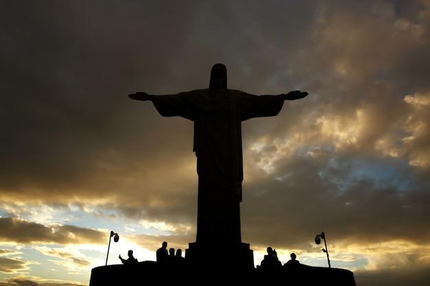 Черный силуэт статуи христа. крест на закатном небе
