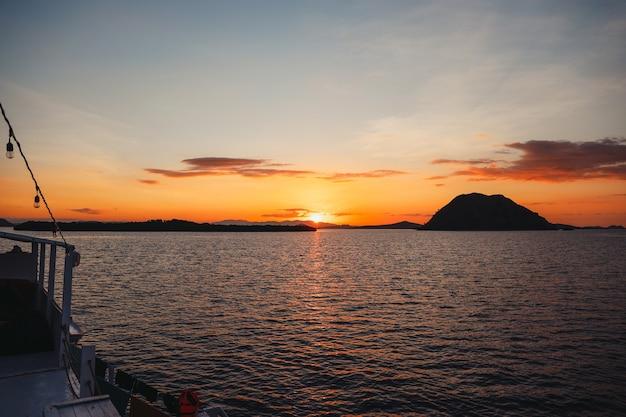 Labuan bajo에서 바다에 태양의 반사와 언덕의 검은 실루엣