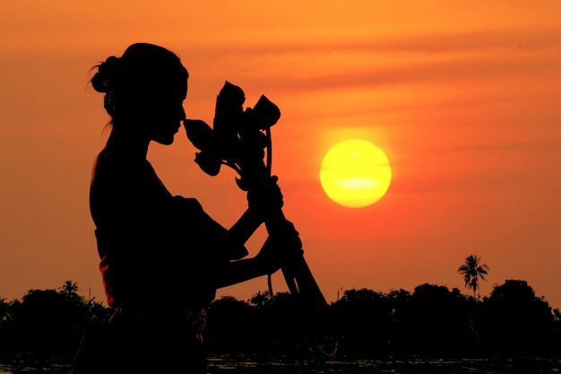 The black silhouette woman standing hugging a lotus flower at sunset