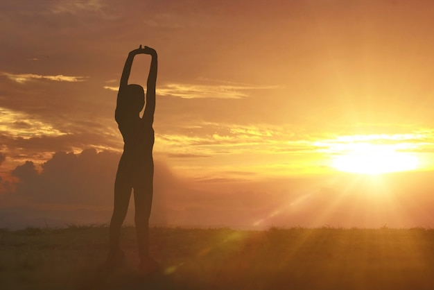 The black silhouette of a young woman with yoga exercises