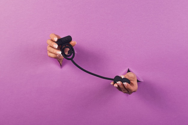 A black silicone sex toy for the clitoris on a pink background in the hands of a woman