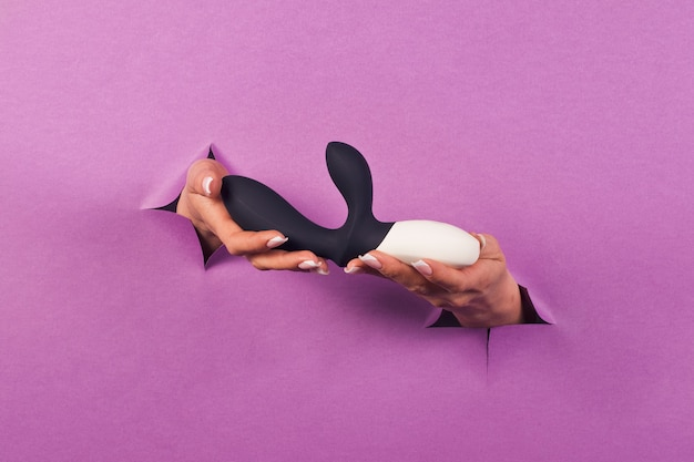 The black silicone sex toy on pink background in female hands erotic toy for fun