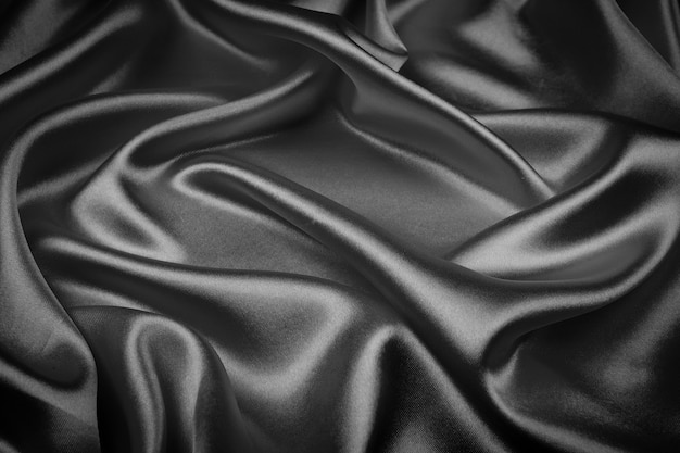 Black silk texture luxurious satin for abstract background. dark tone of fabric