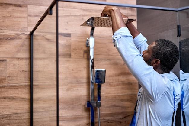 屋内のシャワーバスで働く黒人の熟練したプロの便利屋、側面図の肖像画、水道水栓のシャワー室を設置するオーバーオールのハンサムなプロの配管工、クライアントのバスルームで働く。