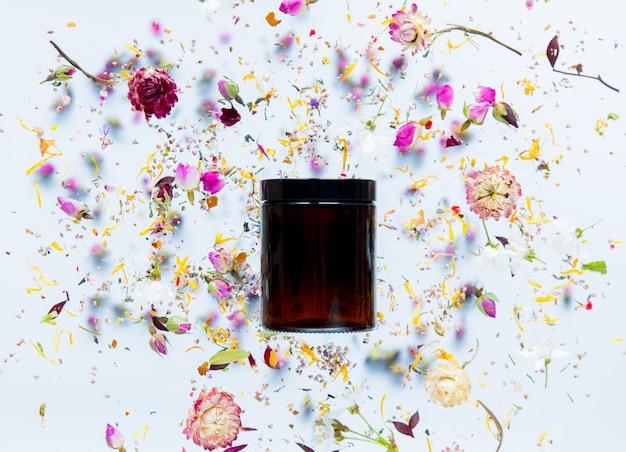 검은 피부 관리 크림 병 및 흰색 표면 주위에 마른 꽃