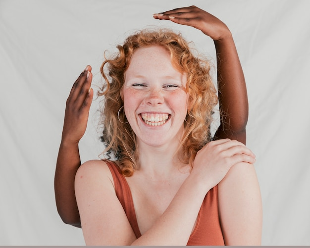Black skinned woman's hand behind the smiling caucasian female friend against grey backdrop