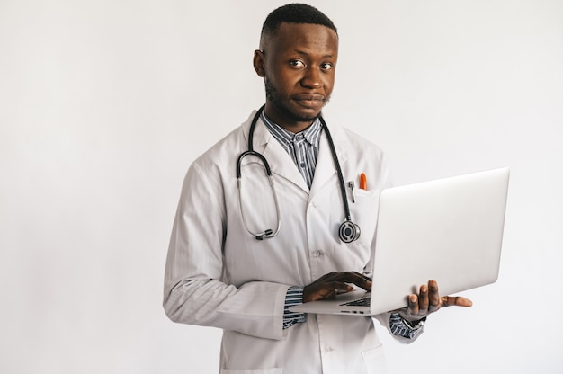 Black skinned young medic smiling standing on a white background with a laptop in his hands.