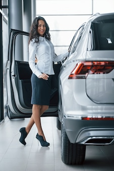 In black skirt. curly haired female manager stands near the car in automobile salon