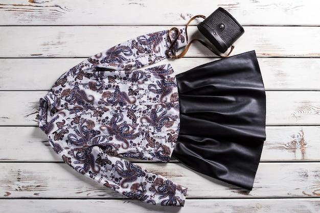 花柄のシャツと黒のスカート。白いテーブルの上のエレガントな服。革のスカートと小さな財布。レトロなハンドバッグと洋服。