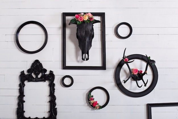 Black skull of a deer and horns on a wooden white wall with empty frames for paintings. the concept of decorating a wooden white wall in the gothic style in the living room. decor, vintage, modern