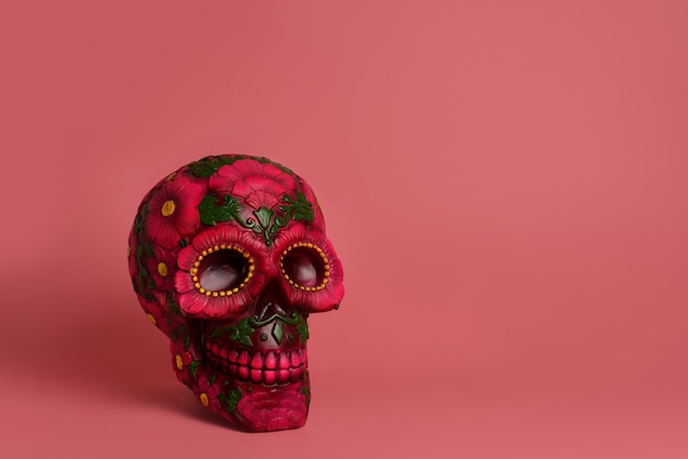 Black skull is decorated with magenta and red flowers