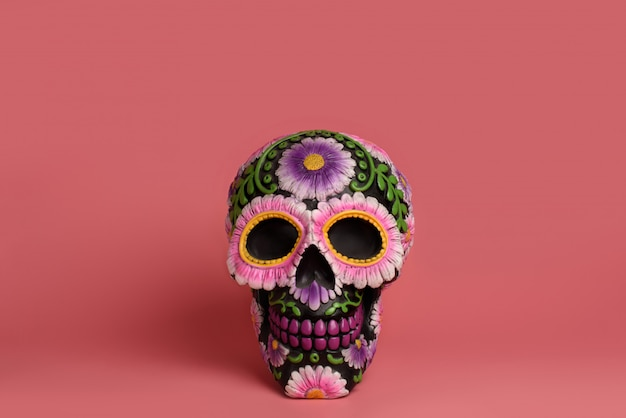 Black skull is decorated with purple and pink flowers
