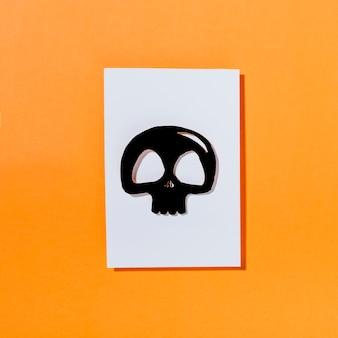 白い紙の上に黒い頭蓋骨
