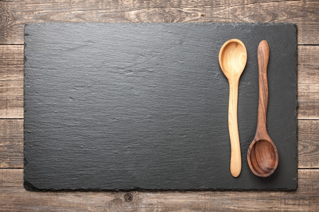 Black slate board with wooden spoons on wooden table