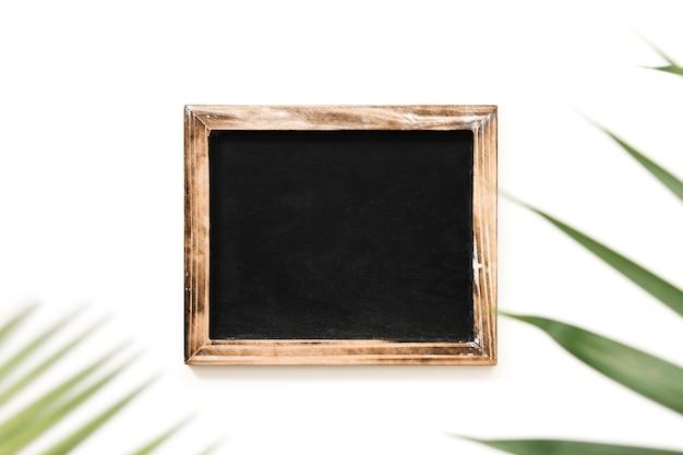 白い背景にパームの葉で飾られた黒いスレート