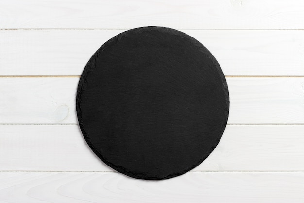 Black slate round stone on wooden background, top view, copy space