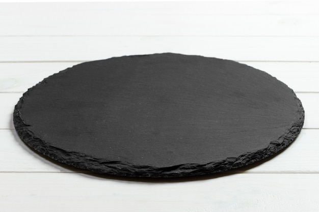 Black slate round stone on wooden background