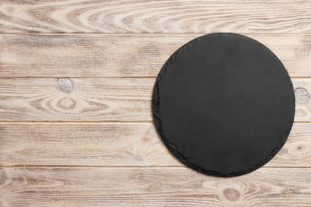 Black slate round stone on wooden surface, top view, copy space