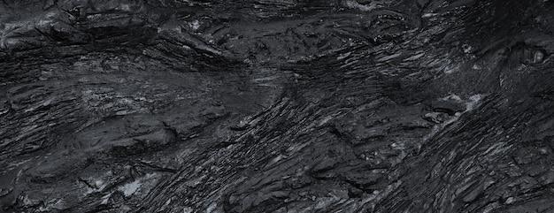 黒のスレートの質感。凹凸のある粗い表面、高さの違い。上面図 Premium写真