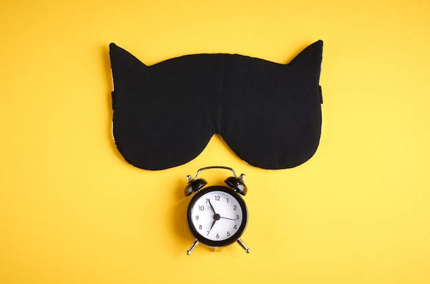 Black sleep mask with clock on yellow composition, cat mask with ears