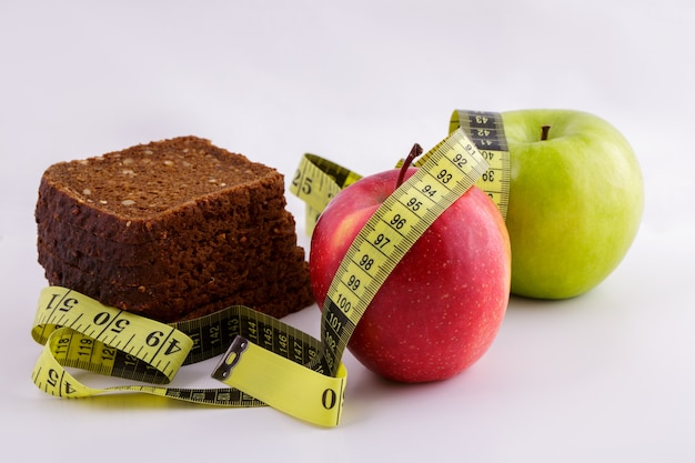 Черный нарезанный хлеб и зеленые и красные яблоки лежат на белом фоне с желтой измерительной лентой d ...