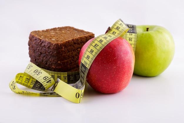 Черный нарезанный хлеб, зеленые и красные яблоки лежат на белой поверхности с желтой измерительной лентой.