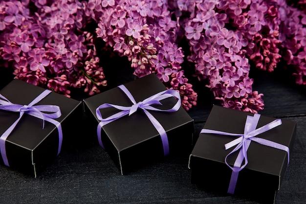 Черные маленькие подарочные коробки обернуты фиолетовой лентой с натуральной сиренью.