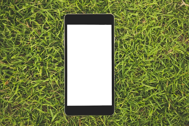 Black smart phone with blank screen on grass