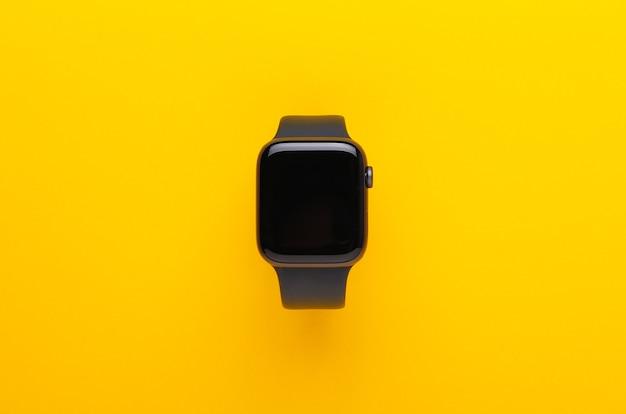 Black smart watch on yellow background.