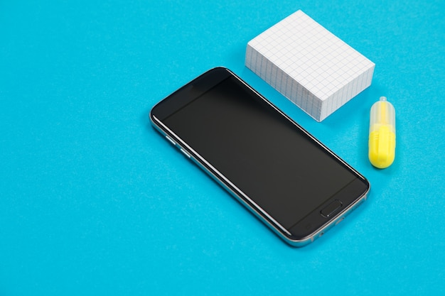Black smartphone, a pile of scratch paper and one yellow textliner on blue background isolated