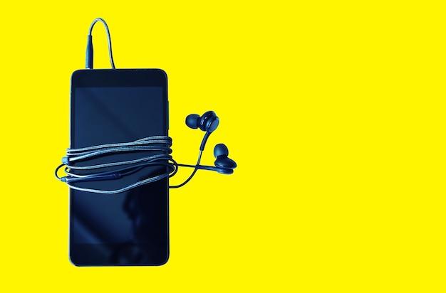 노란색 배경에 이어폰이 분리된 검은색 스마트폰. 현대 기술 연결입니다. 디지털 셀.