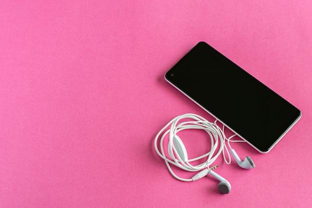 ピンクの背景のイヤホンと黒のスマートフォン